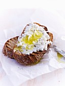 Grilled bread topped with ricotta and olive oil