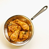 Chicken bit in a red curry sauce in a pan