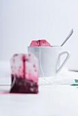 Stillleben mit Teetasse & benutzten Früchteteebeuteln