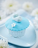 A cupcake decorated with a baby shoe