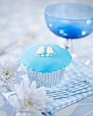 A cupcake decorated with baby feet