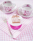 A cupcake decorated with a birdcage and a dove