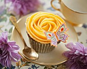 A butterfly cupcake with peach buttercream