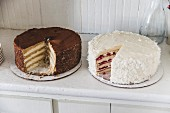 Two layered cakes on a dresser