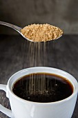 Brown sugar being sprinkled into a cup of coffee