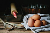 Brown eggs with wood spoons, baking tins and a rolling pin