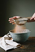 Flour and cake mixture being sieved into a bowl