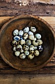 Speckled quail's eggs in a wooden bowl (seen from above)
