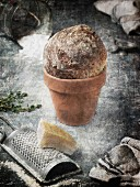 Bread in a terracotta pot and a piece of Parmesan with a cheese grater