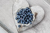 Fresh blueberries in a grey metal bowl on a heart-shaped coaster