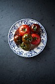 Red and black tomatoes on a plate (seen from above)