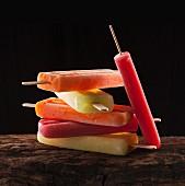 Verschiedene Fruchteis am Stiel gestapelt auf Holzuntergrund