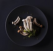 Shimeji mushrooms on a black plate (seen from above)