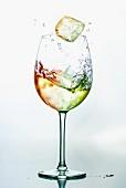 Farbiger Eiswürfel fällt in Weinglas mit farbigem Wein
