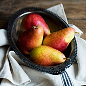 Four pears in a metal bowl