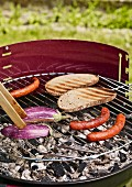 Sausages, aubergines and slices of bread on a barbecue