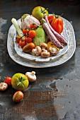 An arrangement of vegetables featuring aubergines, tomatoes, leek and mushrooms