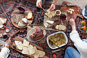 A person eating a picnic-style Christmas meal on a kilim rug