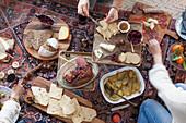 Personen beim Weihnachtsmenü im Picknickstil auf Kelim