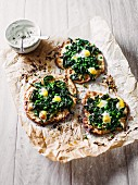 Mini pizzas with quails eggs, spinach and peas served with sour cream
