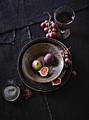 Geschirrstillleben mit Feigen, Weintrauben, Gewürzen und Wein