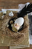 Vintage-style Easter arrangement of duck's egg on cake tin in straw next with quail's eggs and black feather