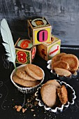 Almond flour and honey biscuits in homemade earthenware cases with building blocks and a feather on a black surface