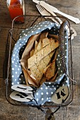 Gluten-free crackers with rosemary and sesame seeds on a blue and white polka dot cloth in a vintage wire basket