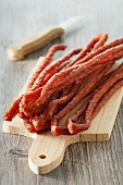 Thin salami sausages on a chopping board