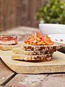Slices of moist rye bread stacked on a chopping board and topped with tomato salad