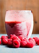 A frozen raspberry smoothie with fresh raspberries