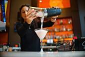 Junge Frau giesst fertigen Cocktail in ein Cocktailglas