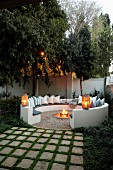 Gemütlicher, kreisförmiger Sitzplatz mit Kissen um Feuerstelle im Garten, Laternen auf gemauerter Rückenlehne in Abendstimmung