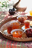 Glasses of tea and candied preserveds fruits on a table outside