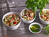 Pasta salad with peas, tomatoes and sausages