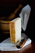Ein Stück Parmesankäse mit Messer auf Marmorplatte