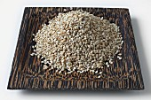 Sesame seeds on a coconut wood dish