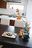 Maki sushi and Inari sushi on table with branch of persimmon fruits