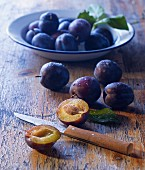 Fresh plums on a plate and on a wooden table, one halved