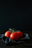 An arrangement of tomatoes with a black napkin