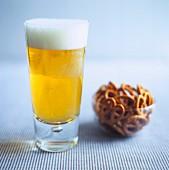 Helles Bier im Glas mit Schälchen Brezeln