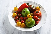 Various different coloured tomatoes on a white plate