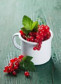 Red currants in an enamel mug