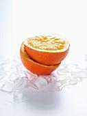 Halbierte Orange auf Eiswürfel
