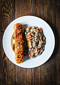 Baked salmon with couscous and vegetables on a wooden surface