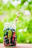 Eistee mit Heidelbeeren im Schraubglas mit Strohhalm auf Gartentisch
