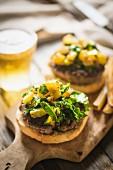 Gegrillter Cheeseburger mit Kartoffeln und Bier auf Schneidebrett