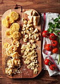 Various types of fresh pasta on a chopping board with Parmesan cheese, tomatoes and coriander