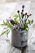 Freshly-picked, flowering herbs in metal mug