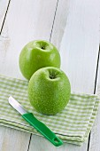 Zwei grüne Äpfel auf Serviette mit Messer
